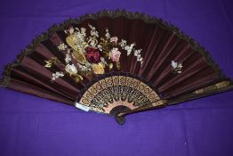 A late 19th/early 20th century maroon silk fan, satin leaf embroidered with basket of flowers and