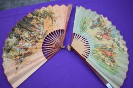Two large paper fans, one having classical scene and gilt detailing to wooden ribs, the second