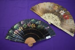 Two hand painted fans having floral scenes to fabric, one having lacquered ribs and the other
