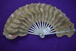 A Victorian fan having hand painted floral paper and gauze like leaves with gilt detailing and