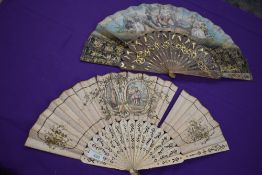 Two lithographic fans, first one having pierced bone ribs and scene of women and rural scenery,