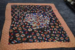 A stunning Victorian patchwork quilt having hexagons to centre surrounded by a border. beautifully