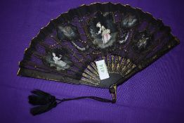 A Victorian black gauze and net fan having painted inserts depicting ladies and countryside scenes.