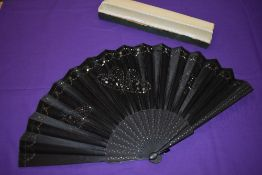 A large boxed early 20th century black silk fan with sequins and spangles forming butterflies to the