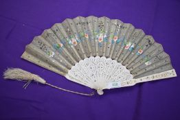 A silver gauze fan painted with flowers and having sequins and spangles, with pierced bone ribs