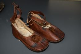 A pair of brown leather baby shoes having pom-pom's to the fronts and strap with button fastening.