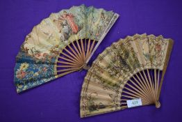 Two paper fans,both having wooden ribs and painted classical scenes, a little wear in places.