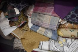A large quantity of upholstery and lining fabrics, high quality fabrics and names, including tartans