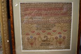 A framed sampler by emma Coupe, aged 10 1862, depicting a deer,alphabet, religious text,and floral