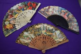 Three colourful paper fans having wooden ribs depicting Spanish scenes and similar, around mid