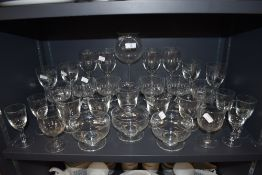 A selection of clear cut and etched glass wares including sundae bowls and wine glasses