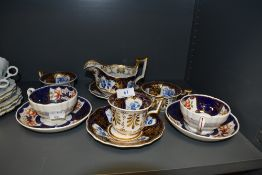 A selection of antique tea cups and milk jug including hard paste with individual hand decorated