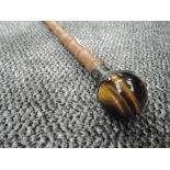 A bamboo shafted walking cane having HM silver ferrule holding Tigers eye stone globe handle