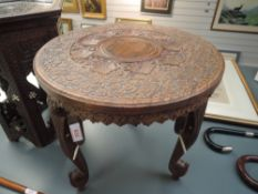 A hand carved Indian table having Elephant head legs and decoration