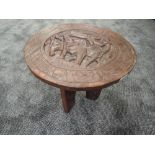 A traditional ethnic wood carved folding table of African design standing 38cm tall