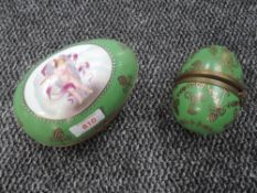 Two ceramic Russian style eggs having cherub decoration with green ground and gold detailing