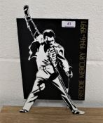 A Freddie Mercury commemorative stand, made from hard plastic, 34cm by 20cm wide.