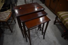 An early 20th Century mahogany and line inlaid nest of three tables on shaped legs, width of largest