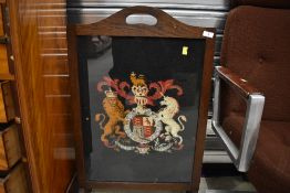 An early 20th Century fire screen having woolwork coat of arms inset