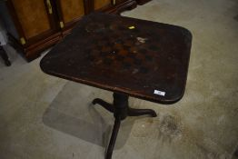 A 19yh Century stained frame pedestal occasional table, with faded chequer board top, some