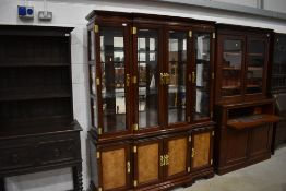 A modern Oriental hardwood bookcase having brass clasps and handles, width approx. 160cm height