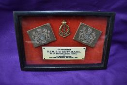 A framed WW2 Memorial consisting of two shoulder badges, cap badge and plaque reading In Memoriam