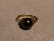 A lady's dress ring having a simulated black pearl flanked by cubic zirconias on a 14ct gold loop,