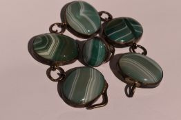 A green stripe agate bracelet having five oval panels in white metal mounts with chain links, no