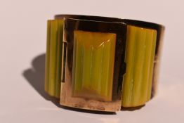 An Art Deco brass and amber style celluloid bangle having a hinged powder compartment to top and a