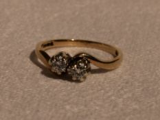 A lady's dress ring having two diamonds, each approx 0.1ct in claw set mounts to crossover shoulders