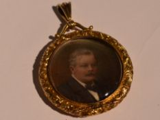 A yellow metal glass locket containing hand painted Edwardian portraits within a decorative