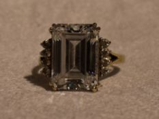 A lady's dress ring having a baguette cut cubic zirconia flanked by two rows of four round cut CZ to