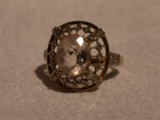 A lady's dress ring having a morganite style oval stone within an open border having diamond chip