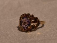 A lady's dress ring having an oval amethyst in a stylised open mount on a 9ct gold loop, size N &