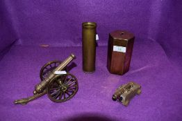 A quirky collection consisting of a brass cannon and similar wooden and brass one,a shell case and a