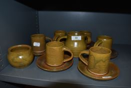A collection of studio pottery including six cups and saucers,jug and sugar basin.