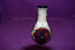 A small baluster shaped Moorcroft vase having pansy design.