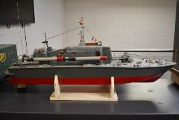 A wooden hand built model radio controlled military boat, painted in grey and with red hull having