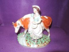 A Staffordshire style figurine depicting milk maid and cow.
