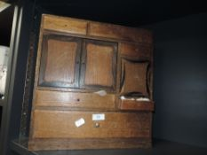 A vintage wooden cabinet with draws of varying sizes and a miniature cupboard housing a selection of