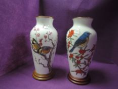 Two large Franklin porcelain vases with stands having birds,flowers and berries to fronts.