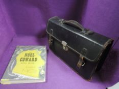 A selection of piano sheet music and Noel Coward song book with leather bound satchel