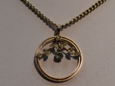 An Edwardian yellow metal pendant stamped 9ct of circular form having seed pearl decoration with