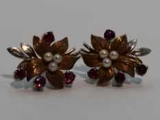 A pair of 9ct white and yellow gold stud earrings modelled as leaves having ruby and seed pearl