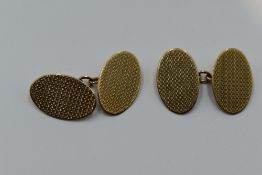 A pair of 9ct gold cufflinks of oval form having engine turned chequered decoration and chain