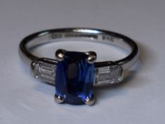 A lady's 1930's dress ring having a central cushion cut sapphire, approx 1.65ct flanked by two
