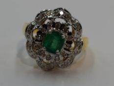 A lady's dress ring having a central emerald within a frilled double cluster of small diamonds in
