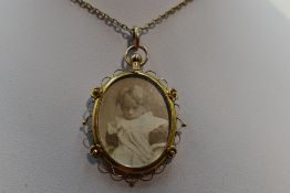 A glass locket of oval form having a decorative 9ct gold mount on a yellow metal chain stamped 9ct