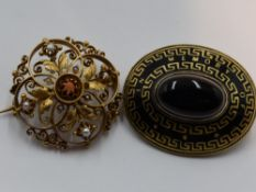 A yellow metal brooch having central coral pearl within an open foliate and scroll mount having seed