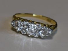 A Victorian lady's dress ring having three graduated diamonds with a border of six diamond chips,